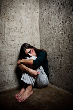 battered woman cowering in a corner
